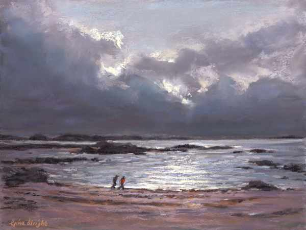 Two people on beach with storm clouds behind them