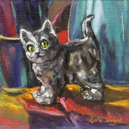 Still life of grey cat statuette on multi-coloured fabric